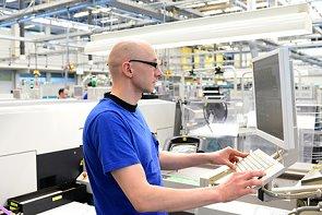 Ingenieur in Fabrik steuert Maschine in der HiTech Fertigung